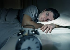 man in bed with eyes opened suffering insomnia sleep disorder