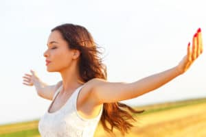 Portrait of beautiful young woman in field with her arms outstretched.